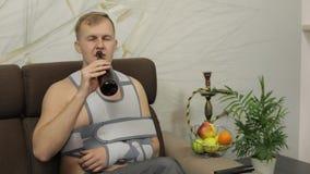 Homem doloroso com uma cinta vestindo do bra?o do bra?o quebrado que senta-se em uma cerveja das bebidas do sof? video estoque
