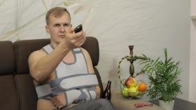 Homem doloroso com uma cinta vestindo do bra?o do bra?o quebrado que senta-se em um sof? que olha a tev? filme