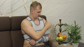 Homem doloroso com uma cinta vestindo do bra?o do bra?o quebrado que senta-se em um sof? que olha a tev? video estoque