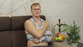 Homem doloroso com uma cinta vestindo do bra?o do bra?o quebrado que senta-se em um sof? que olha a tev? vídeos de arquivo