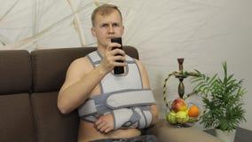 Homem doloroso, furado com uma cinta vestindo do braço do braço quebrado que senta-se em um sofá video estoque