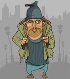 Homem dos desenhos animados na roupa áspera com uma trouxa na cidade Imagens de Stock Royalty Free