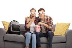 Homem e adolescentes fêmeas que olham um filme 3d e que comem a pipoca fotos de stock royalty free