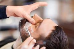 Homem e barbeiro com a lâmina reta que barbeia a barba imagem de stock