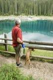 Homem e cão pelo lago azul Imagem de Stock Royalty Free