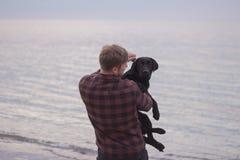 Homem e cão preto na praia Foto de Stock