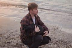 Homem e cão preto na praia Fotos de Stock