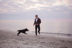 Homem e cão preto na praia Fotografia de Stock Royalty Free