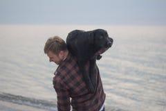 Homem e cão preto na praia Imagem de Stock Royalty Free