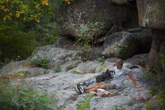 Homem e cão Schnauzer diminuto perto da garganta Enjoing o tempo fora Árvores e montanhas verdes no fundo Imagens de Stock Royalty Free