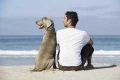Homem e cão que sentam-se na praia Imagens de Stock