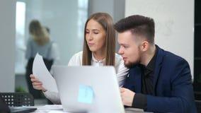Homem e colegas de sorriso fêmeas que discutem trabalhando o assento na tabela no escritório moderno usando o portátil video estoque