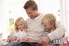 Homem e crianças que lêem junto Fotografia de Stock