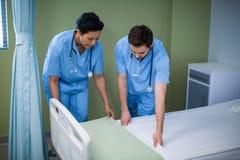 Homem e enfermeira fêmea que preparam a cama para o paciente imagens de stock
