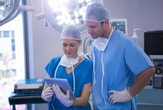 Homem e enfermeira fêmea que usa a tabuleta digital no teatro de operação fotografia de stock royalty free