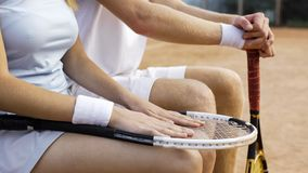 Homem e fêmea no sportswear que senta-se no banco na corte após o fósforo do tênis fotos de stock