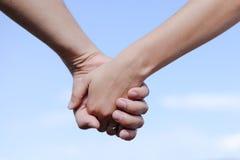 Homem e fêmea que guardam as mãos fora sobre um azul Imagens de Stock Royalty Free