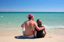 Homem e filha que sentam-se na praia abandonada ensolarada Fotografia de Stock Royalty Free
