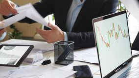Homem e mãos fêmeas da equipe do negócio que analisam relatórios financeiros na mesa Braços dos executivos que examinam gráficos video estoque