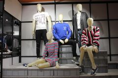 Homem e manequins fêmeas na forma ocidental indicada em uma loja de roupa em um shopping imagem de stock
