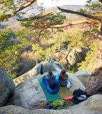 Homem e menina do turista que sentam-se em uns sacos-cama na rocha grande da montanha fotos de stock royalty free