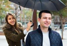 Homem e menina que sorriem sob o guarda-chuva fora Imagens de Stock