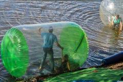 Homem e menina Zorb dentro das grandes bolas do ar no rio Fotografia de Stock