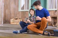 Homem e menino com os copos do chá que olham se Fotos de Stock