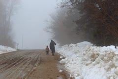 Homem e menino que andam abaixo da estrada do cascalho no inverno fotografia de stock royalty free