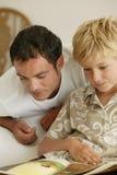 Homem e menino que lêem um livro Fotos de Stock Royalty Free