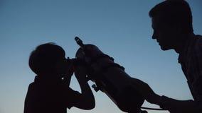 Homem e menino que usa o telescópio filme