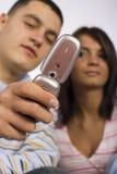 Homem e mulher adultos novos com telefone de pilha Fotografia de Stock