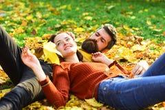 Homem e mulher com as caras felizes na grama e nas folhas Fotos de Stock