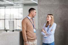 Homem e mulher com crachás da conferência no escritório imagens de stock