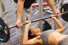 Homem e mulher com o barbell que dobra os músculos no gym fotografia de stock