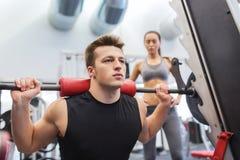 Homem e mulher com o barbell que dobra os músculos no gym fotos de stock