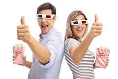 Homem e mulher com os vidros 3D e a pipoca que mantêm os polegares Imagem de Stock Royalty Free