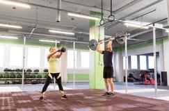 Homem e mulher com pesos que exercitam no gym fotografia de stock royalty free
