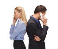 Homem e mulher com telefones celulares Fotos de Stock Royalty Free