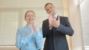 Homem e mulher de dois homens de negócios que aplaudem em um escritório em um fundo da janela com obturadores aplauso filme