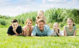 Homem e mulher de riso com as crianças que encontram-se no parque fotos de stock