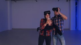 Homem e mulher de riso nos auriculares da realidade virtual que olham suas fotos engraçadas no telefone Imagens de Stock