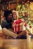 Homem e mulher de sorriso que trocam presentes de Natal imagem de stock