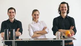 Homem e mulher do barman de Professinal que sorriem na tabela móvel da barra no estúdio branco do fundo imagens de stock
