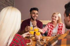 Homem e mulher do grupo dos jovens que sentam-se no café do hamburguer, brindando a tabela de madeira alaranjada de Juice Order F Fotografia de Stock