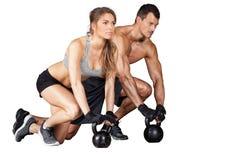 Homem e mulher do treinamento de Kettlebell imagens de stock royalty free