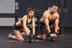 Homem e mulher do treinamento de Kettlebell Imagem de Stock