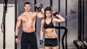 Homem e mulher do treinamento de Kettlebell em um gym Imagem de Stock