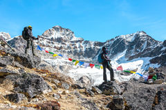 Homem e mulher em ficar alpino dos montanhistas roupa e da engrenagem Imagem de Stock