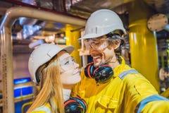 Homem e mulher em um uniforme amarelo, em vidros, e em capacete do trabalho em um ambiente industrial, em uma plataforma petrol?f foto de stock royalty free